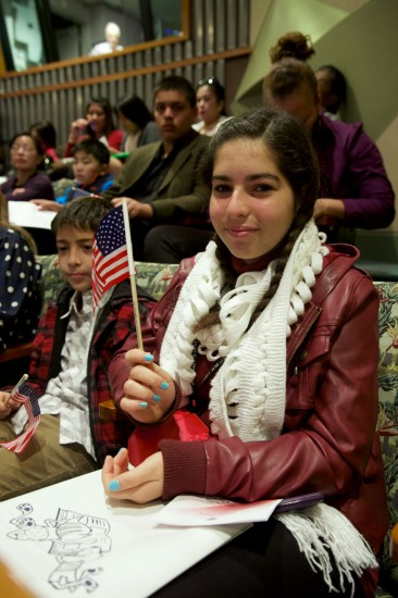 Girl at a naturalization ceremony holding the American flag.