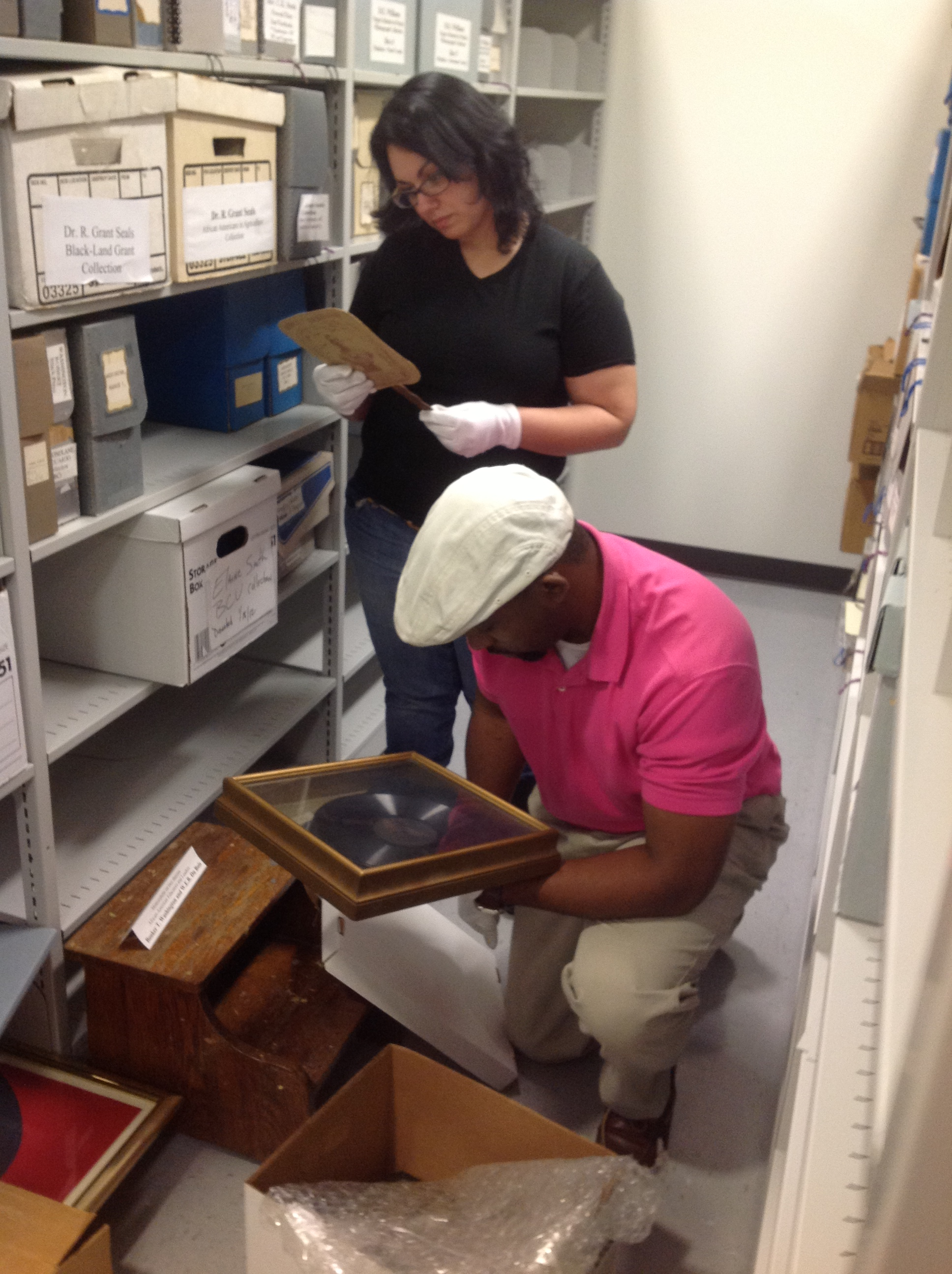 Students pull materials from archival stacks.
