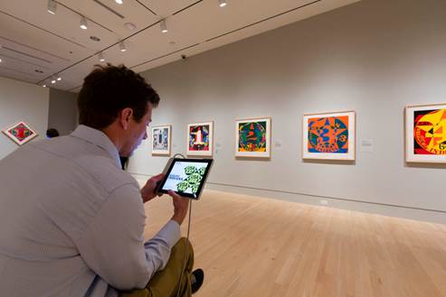 Visitor using an iPad in an art gallery,