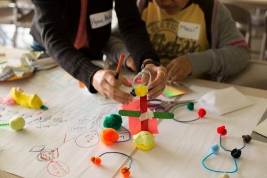 Kids working on a design at a Teen Design Day workshop.