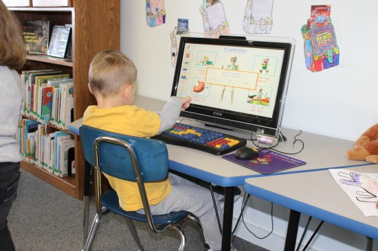 A child sits at a computer