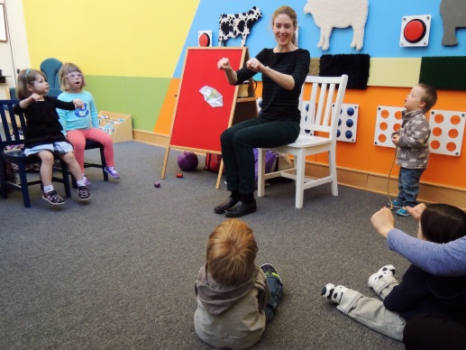 A librarian sits at the front of a program teaching children.