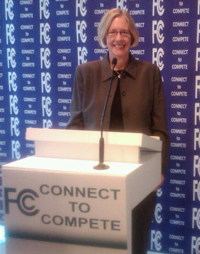 """photo of Susan Hildreth behind a """"Connect to Compete"""" podium"""