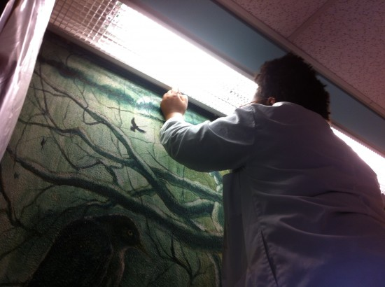 LaStarsha McGarrity working on a mural by Kermit Oliver.