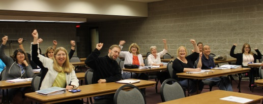 Librarians sitting in a classroom raising their hands.