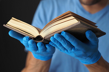 Book in men's hands in blue medical gloves.