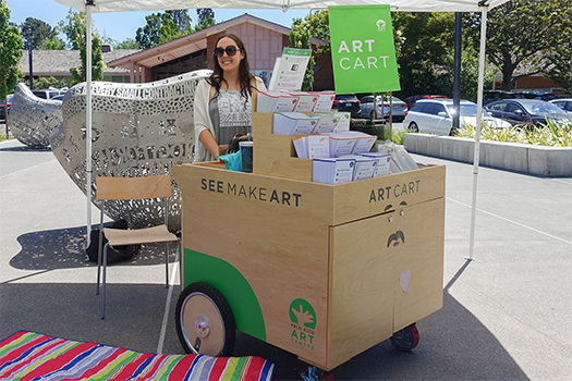Museum staffer outside with art cart