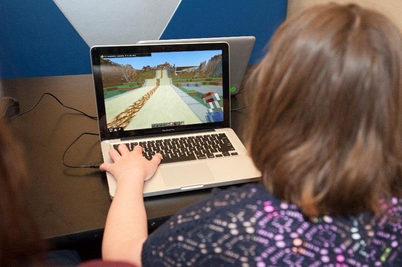 Teen playing Minecraft on laptop