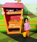 Little girl hold an egg in front of a chicken coop display