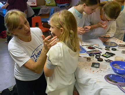 (Pictured: Samantha Norton of the Bloomsburg Theater Ensemble teaches a student how makeup is used to simulate a bruise in stage productions. Photo Courtesy of The Children's Museum)
