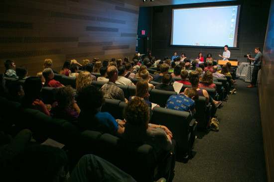 An auditorium filled with people with the student poets at a front panel table.