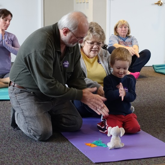 child and grandparent warming their hands in a yoga class