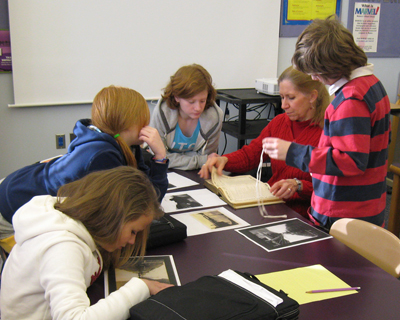 photo of a teacher and students around a table, looking at documents and photographs