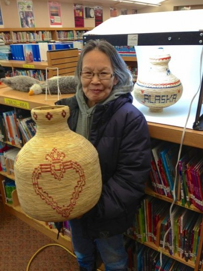 Chevak village elder Maggie Atcherian and her grandson Matt Atcherian display her native artwork for sale online.