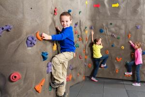 A young boy climbing a rock wall.