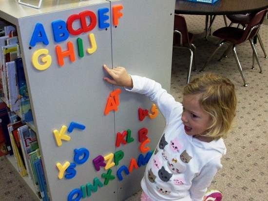 A young girl with alphabet magnets