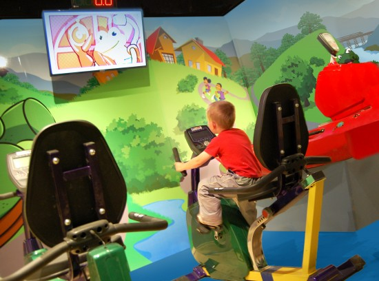 """A child rides a bike in the """"League of Healthy Heroes"""" exhibition at Amazement Square."""