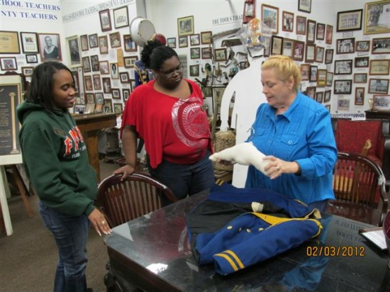 Mrs. Cheryl Walters, the part-time registrar hired with IMLS funds, demonstrates conservation techniques to Ms. Brittanye Jacobs, FAMU intern, who joined the museum as a result of the IMLS grant. Also pictured is Laketia Bates, part-time staff person responsible of entering data into the museum