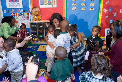 Photo of Mrs. Obama in a child care center, receiving hugs from several children.