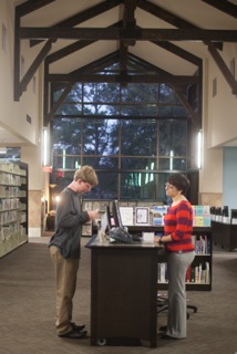 Photo of a librarian helping an autistic teenager.