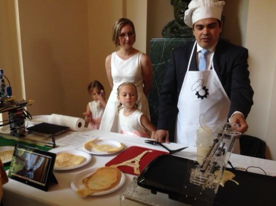 """A man makes pancakes with a """"pancake bot: device"""""""