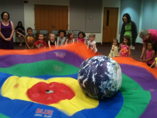 Children holding a parachute and bouncing a ball