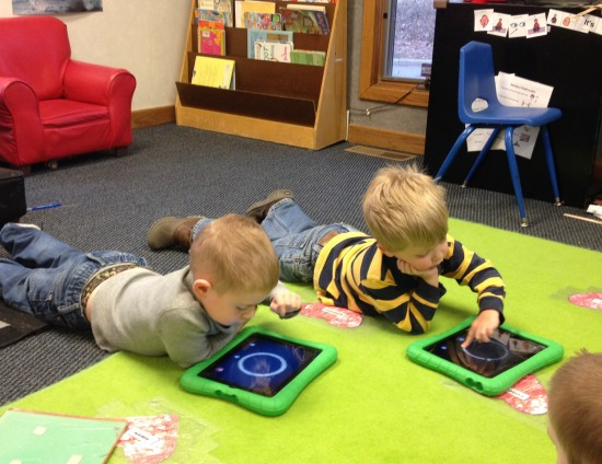Children in a library playing on iPads