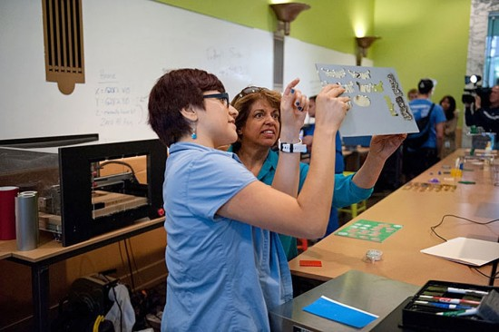 A member of the Chicago Public Library staff shows a patron what can be done with a 3D printer in their Maker Lab.