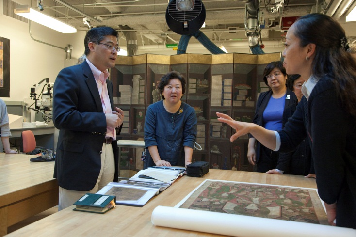 Visiting conservators discuss a Korean painting