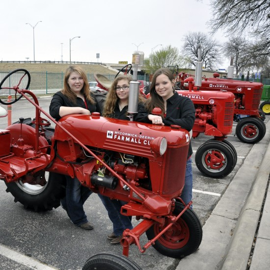 Students from Utopia, TX ISD Future Farmers of America Program stand behind their tractors.