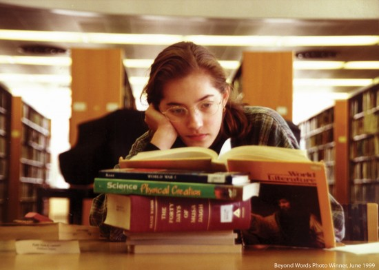 Girl reading books in library.