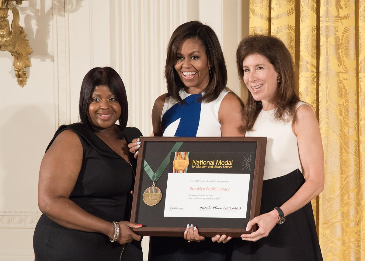 First Lady Michelle Obama presents the award to community member Kim Best and Brooklyn Public Library President and CEO Linda E. Johnson.