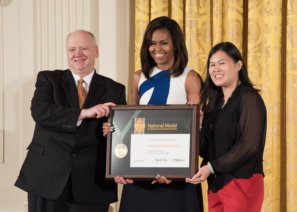 Representatives from the Chicago History Museum, President Gary T. Johnson and community member Joyce Chiu, accept the award from First Lady Michelle Obama.