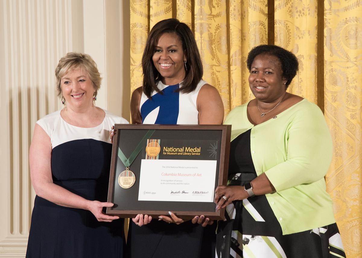 First Lady Michelle Obama presents the award to Columbia Museum of Art Director Karen Brosius and community member Joyce Rose-Harris.