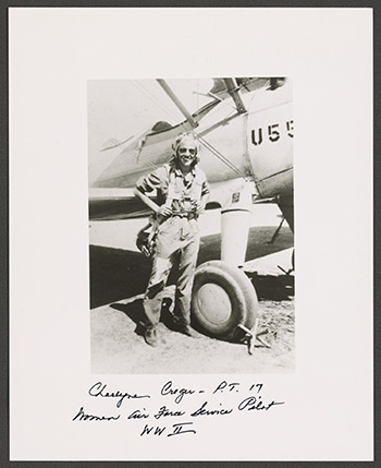 Charlyne Creger wearing a flight suit and goggles and carrying a rucksack posing in front of an airplane