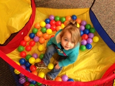 child in a tent of balls
