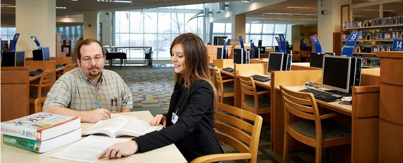 Image of two people learning in a library