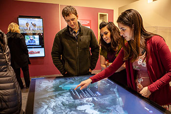 """Visitors use the interactive map at the Sealaska Heritage Institute's exhibit """"Our Grandparents' Names on the Land""""."""