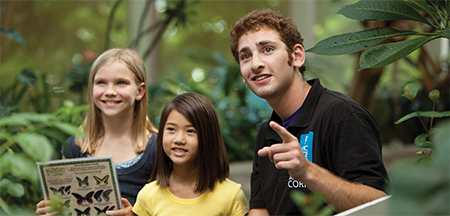 A staff member points out tropical butterflies at the Pacific Science Center in Seattle, WA.
