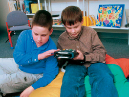 Two boys use talking book in a library
