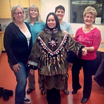 museum staff stand behind a student wearing the finished parka