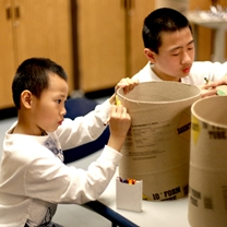two boys decorate their drums
