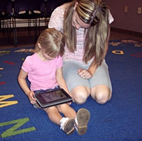 a young girl uses an e-reader