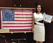 Susan Simons holds her U.S. Naturalization certificate in front of a historical American flag