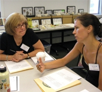 Two teachers converse at a table; musuem collections are visible in the background.