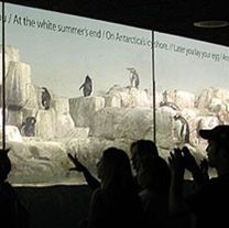 Central Park Zoo visitors read poetry while viewing penguins.