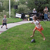 Kids run and play in front of an outdoor musical performance