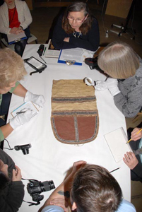 museum sewers examine sewn pieces around a table