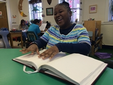 Shaniya Harcum reading a Braille book