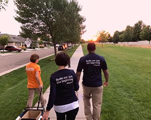 Three library volunteers walking outdoors.